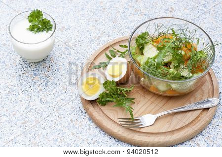Salad with fresh vegetables and herbs in a glass bowl on a wooden board, boiled eggs and yogurt