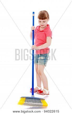 Little girl sweeping debris brush