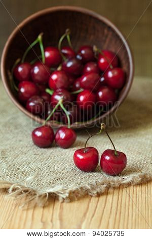 Healthy organic vegetarian super food cherries in clay dish on rustic kitchen table background