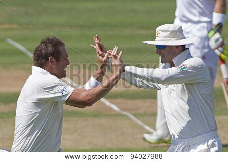 LONDON, ENGLAND - July 18 2013: Ryan Harris and Michael Clarke celebrate the wicket of Jonathan Trott on day one of the Investec Ashes 2nd test match, at Lords Cricket Ground on July 18, 2013