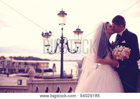 Bride And Groom Kissing Near Street Lights