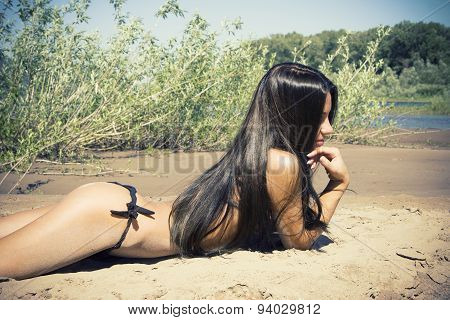 Smiling Beautiful Woman Sunbathing Topless On A Beach