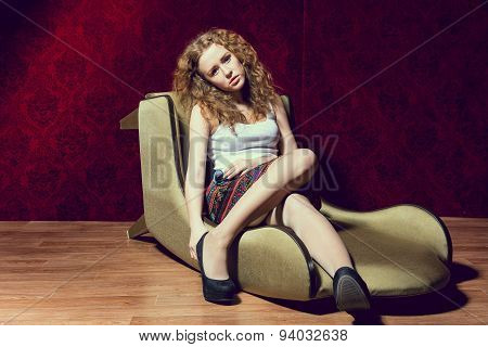 Sad Young Girl Sitting On A Chair On A Red Background