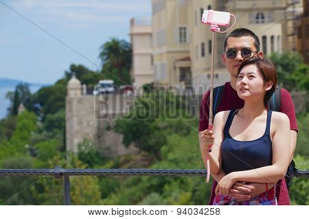 Asian couple make selfie with a smartphone on a stick at the viewpoint in Monaco.
