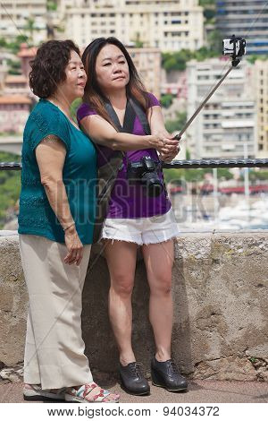 Asian women make selfie with a smartphone on a stick at the viewpoint in Monaco.