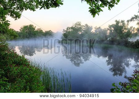 Nice foggy landscape with river at early morning time