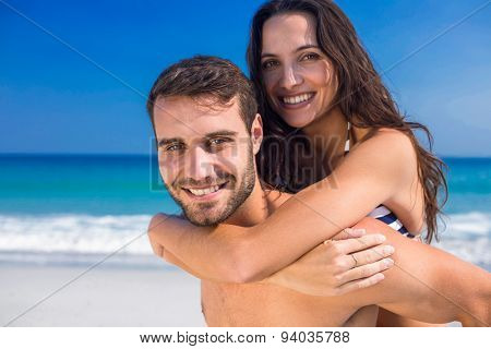 Man giving piggy back to his girlfriend at the beach on a sunny day