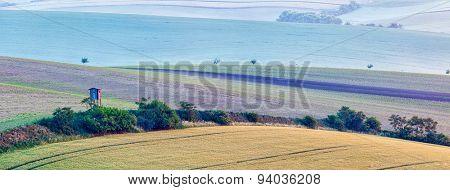 Rural Europe background - panorama of Moravian rolling landscape with hunting tower shack in early morning on sunrise. Moravia, Czech Republic