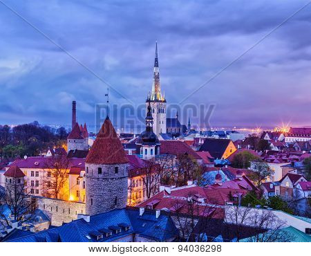 Aerial view of Tallinn Medieval Old Town with St. Olaf's Church and Tallinn City Wall illuminated in evening, Estonia