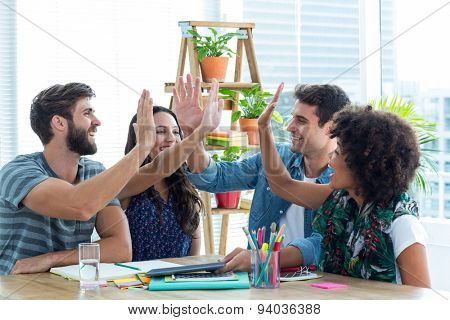 Creative business team putting their hands together in meeting at office