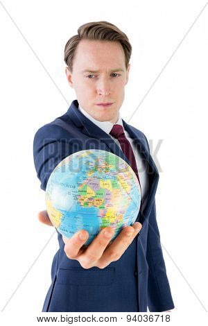 Serious businessman holding terrestrial globe on white background