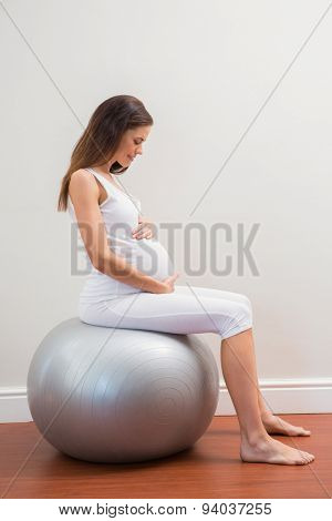 Happy pregnancy sitting on exercice ball in a room