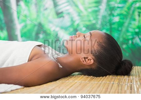 Pretty woman lying on massage table with salt scrub on the chest