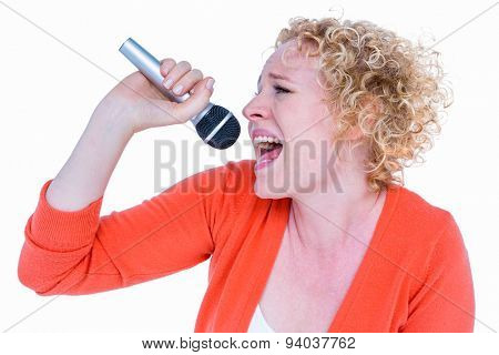 Happy pretty blonde singing in microphone on white background