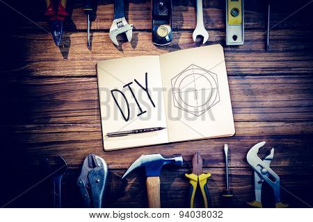 The word diy and notebook and pen against blueprint