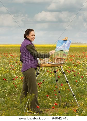 artist paints picture with brush  on the poppy field