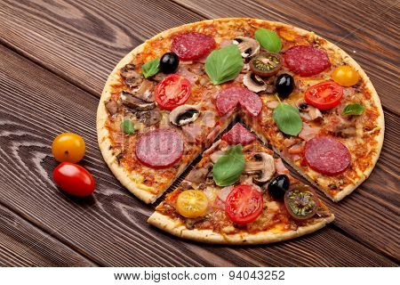 Italian pizza with pepperoni, tomatoes, olives and basil on wooden table