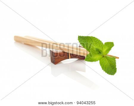 Sushi chopsticks with mint leaves. Isolated on white background