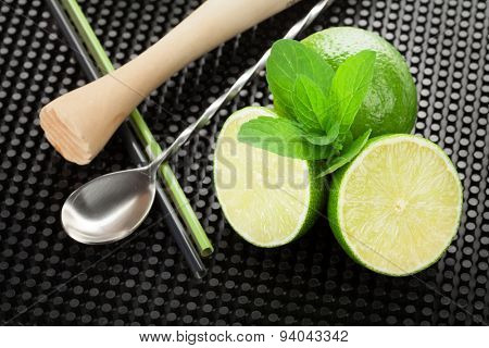 Mojito cocktail ingredients and utensils on black rubber mat