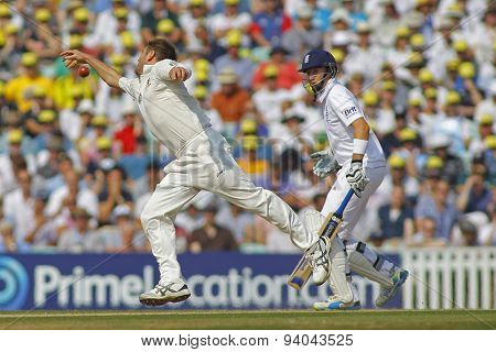 LONDON, ENGLAND - August 23 2013: Ryan Harris fails to stop the ball as Joe Root looks on during day three of the 5th Investec Ashes cricket match between England and Australia
