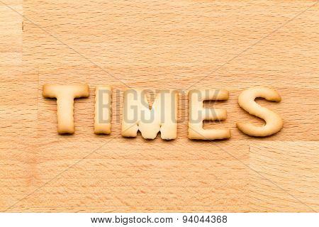 Word times biscuit over the wooden background