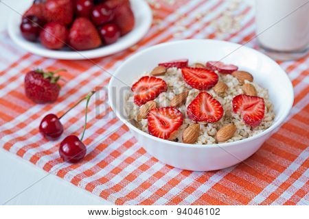 Helathy breakfast oatmeal porridge with strawberry, cherries and almond nuts in white dish on kitche