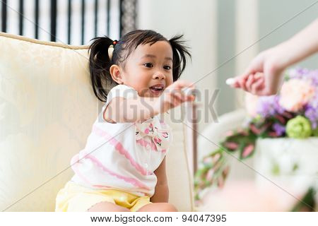 Mother give the finger food to her daughter