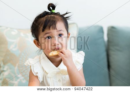 Little girl sitting and eatting food on the couch