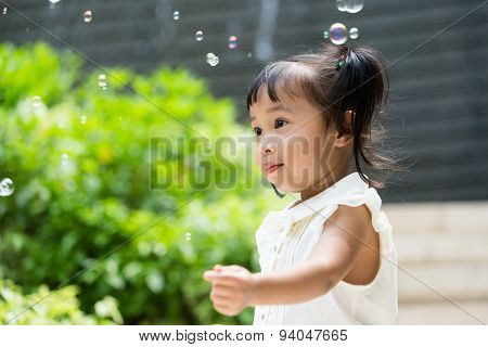 Asian baby girl play bubble blower at outdoor