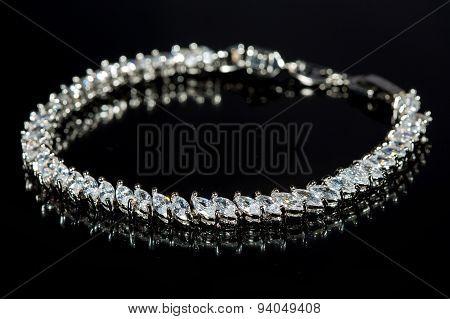 silver bracelet with diamonds on black background.