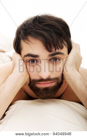Depressed young man lying in bed.