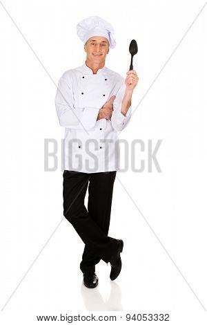 Restaurant chef holding black plastic spoon