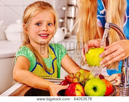 Happy children washing fruit at kitchen.