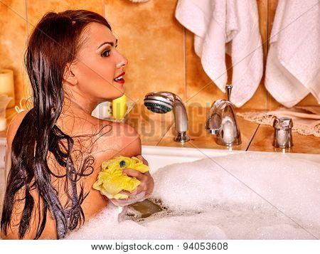 Young woman using bath sponge in bathtub.