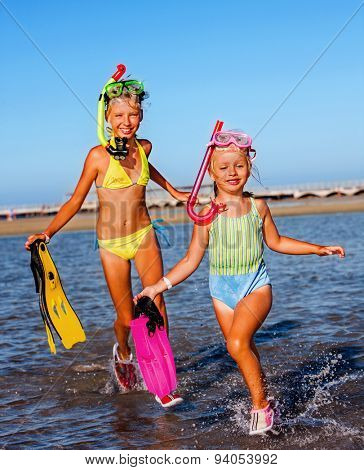 Children running on  beach for snorkeling.