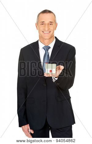 Happy businessman holding house model.