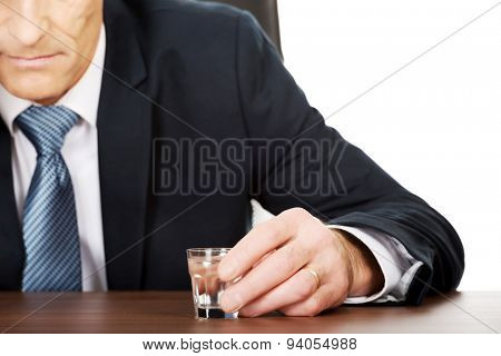 Overworked man drinking vodka in office.