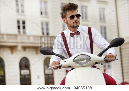 Hipster fashion men with scooter on a sunny day in the city