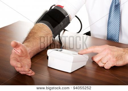 Closeup on businessman measuring blood pressure.