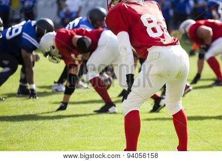 American football game. Out of focus players in the background