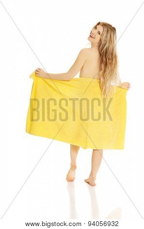 Woman standing with a towel back to camera.