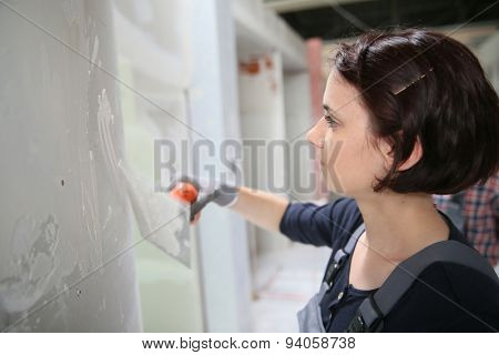 Young plasterer working on indoor wall