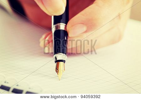 Handwriting, hand  writes with a pen in a notebook