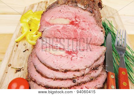 roasted meat served on wooden plate with vegetables