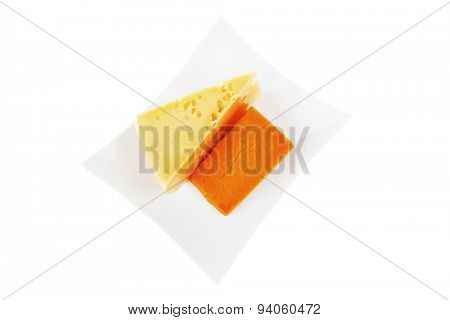 fresh dairy product : gourmet cheese triangles of yellow parmesan and orange cheddar on a plate isolated over white background