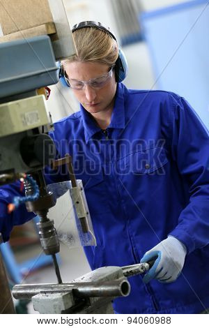 Metalworker making holes in steel tubes with machine