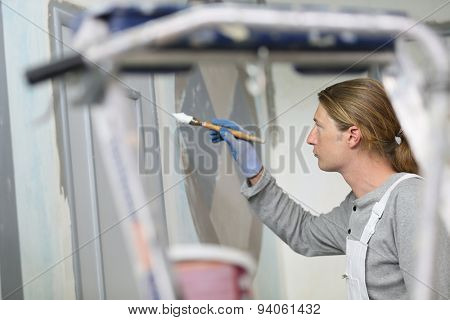 Professional painter painting room wall