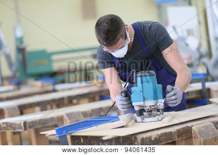 Young carpenter working on piece of wood with sawing machine