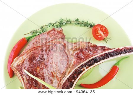 meat food : grilled beef spare rib on green dish with thyme pepper and tomato isolated over white background