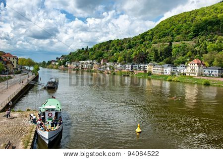 HEIDELBERG, GERMANY - APRIL 26: Tour Boats and Buildings on River Banks of Neckar River, Heidelberg, Baden-Wurttemberg, Germany Framed by Lush Green Hillsides on April 26, 2015